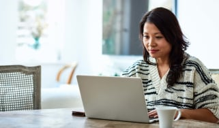 A woman sits at a dining room table with a laptop and a cup of coffee.