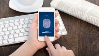mains féminines tenant un téléphone tactile blanc sur le bureau du bureau et entrant le code PIN de l'empreinte digitale