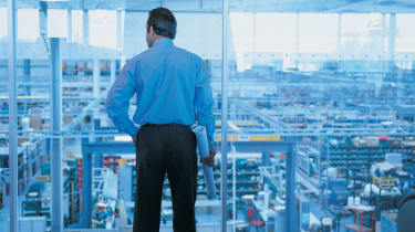 A business executive looks out of his office windows at the city below