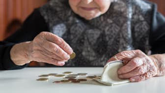 picture of elderly woman counting coins out of her change purse