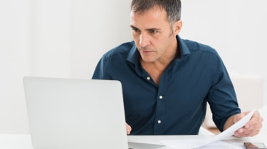 Portrait Of A Mature Man Looking At Laptop Holding Document