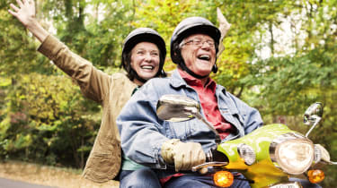 Happy senior couple traveling down road on motor scooter.