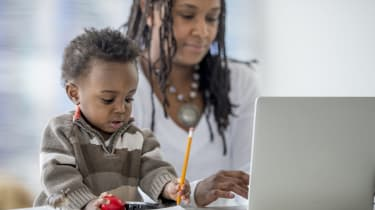 A woman of African descent is at home with her baby boy. She is working from home on her laptop. Her son is playing with a pencil and toy car beside her.