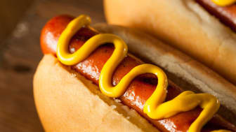 A cooked hot dog with mustard on a bun