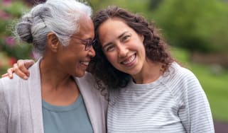 A woman leans her head on the shoulder of her grandmother