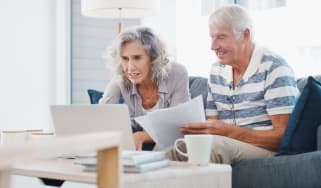 Senior couple working with paperwork and on laptop estate-planning