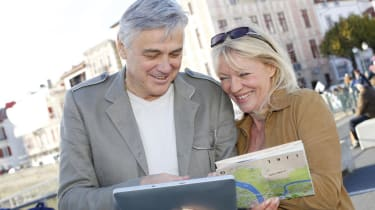 Senior couple visiting old city with map and tablet
