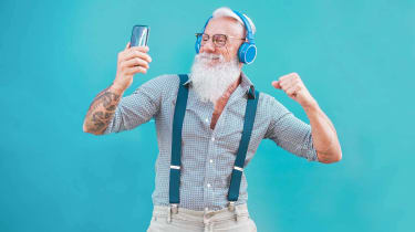 Man with white beard wearing headphones