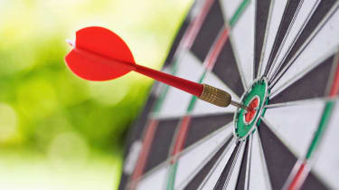 Darts in center of the target dartboard on a light green background