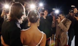 The paparazzi photograph a glamorous couple.