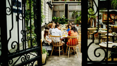 A family meets around a table on a terrace.