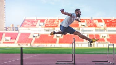 35 years old man at the stadium. He is jumping over the hurdle, and improving his jumping skills