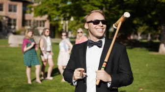picture of rich guy holding a croquet mallet and smoking a cigar