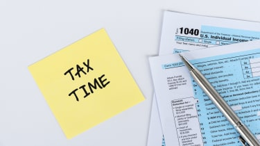 """picture of a post-it note with """"tax time"""" written on it next to some tax forms and a pen"""