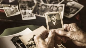 picture of an elderly woman's hands holding an old photo of a man in uniform