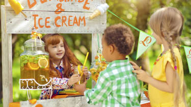 Little girl selling lemonade from a lemonade stand outdoors in summer to children