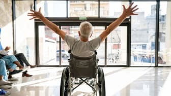 A man in a wheelchair raises his arms in celebration.