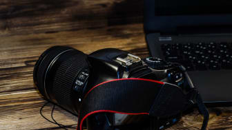 Modern DSLR camera and laptop on rustic wooden table