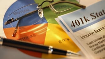 A 401K statement on a pie chart suggesting proper asset allocation. A strong directional light plays across the scene.A pair of eyeglasses and a ballpoint pen sit on the pie chart. Image is s