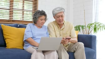 A couple looking at a computer and a credit card