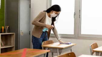 picture of teacher disinfecting a desk