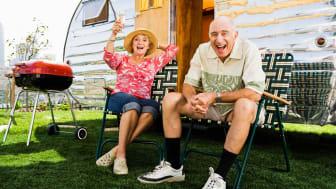 Fun senior couple laugh and toast outside their RV
