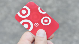 Vancouver, British Columbia, Canada -- August 23, 2014:Close up of a man holding a Target Gift Card in his hand. Target is an American discount retail chain that recently expanded to Canada.