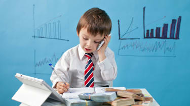 Young boy, talking on the phone, taking notes, money and tablet on the table