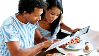 Afro American couple calculating their home expenses at the breakfast table
