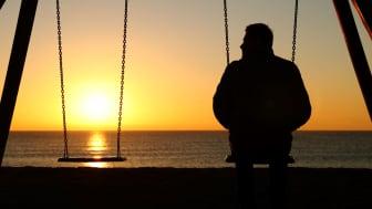 A man sits alone on a swing.
