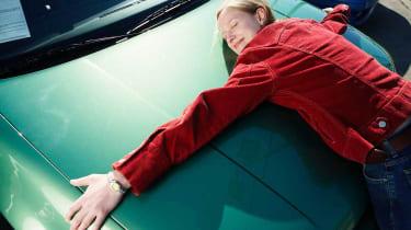 A car-shopping woman hugs the hood of a new car.