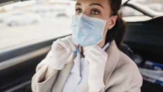 A female healthcare worker putting a protective mask over her nose and mouth while wearing protective gloves as well. She is sitting in her car, preparing to commute to work at the NHS.