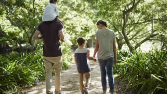 Full length rear view of two generation family walking on path in park