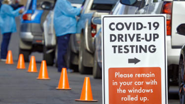 Cars wait in line at a COVID-19 drive-up testing station