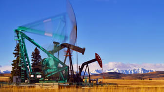 Pumpjacks in motion, showing movement. A foothills and mountain location with blue sky and fluffy clouds.