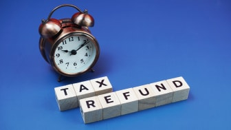 """picture of an alarm clock with letter tiles spelling """"tax refund"""""""
