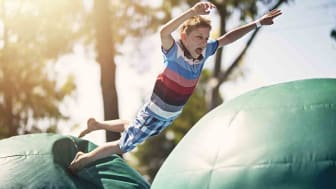 Little boy having fun in inflatable bouncy castle playground. Sunny summer dayNikon D810