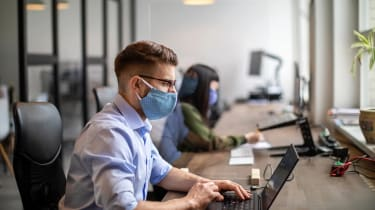 Business people back to work after pandemic sitting at desk with protection guard between them