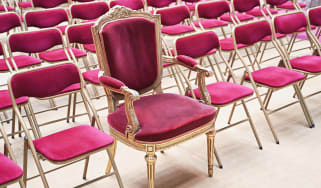 A fancy throne sits in a line of folding chairs.