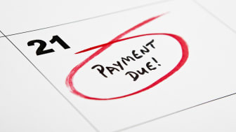 Image of a payment due date noted down on a calendar and circled in red.