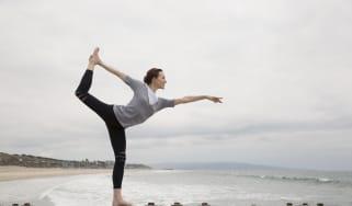 Woman doing yoga king dancer pose on beach