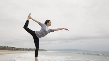 Woman doing yoga king dancer pose on beach