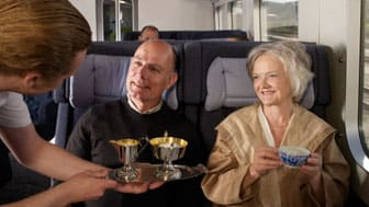 Waiter serving couple on train