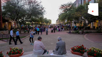 An older couple sit at a fountain in downtown Surprise, Ariz.
