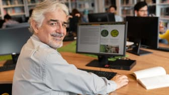 Retiree in college library on laptop looks back and smiles at camera