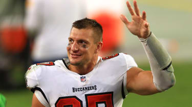 NFL star Rob Gronkowski smiles and waves as he walks of the field.