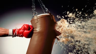 picture of man punching punch bag and stuffing exploding from bag
