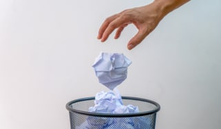 A hand throws a balled up piece of paper in a waste basket.
