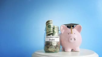 picture of piggy bank wearing graduation hat next to jar of money