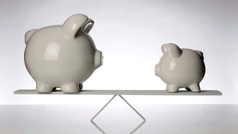 A large piggy bank and a small piggy bank on opposite sides of a teeter totter, illustrating a middle ground